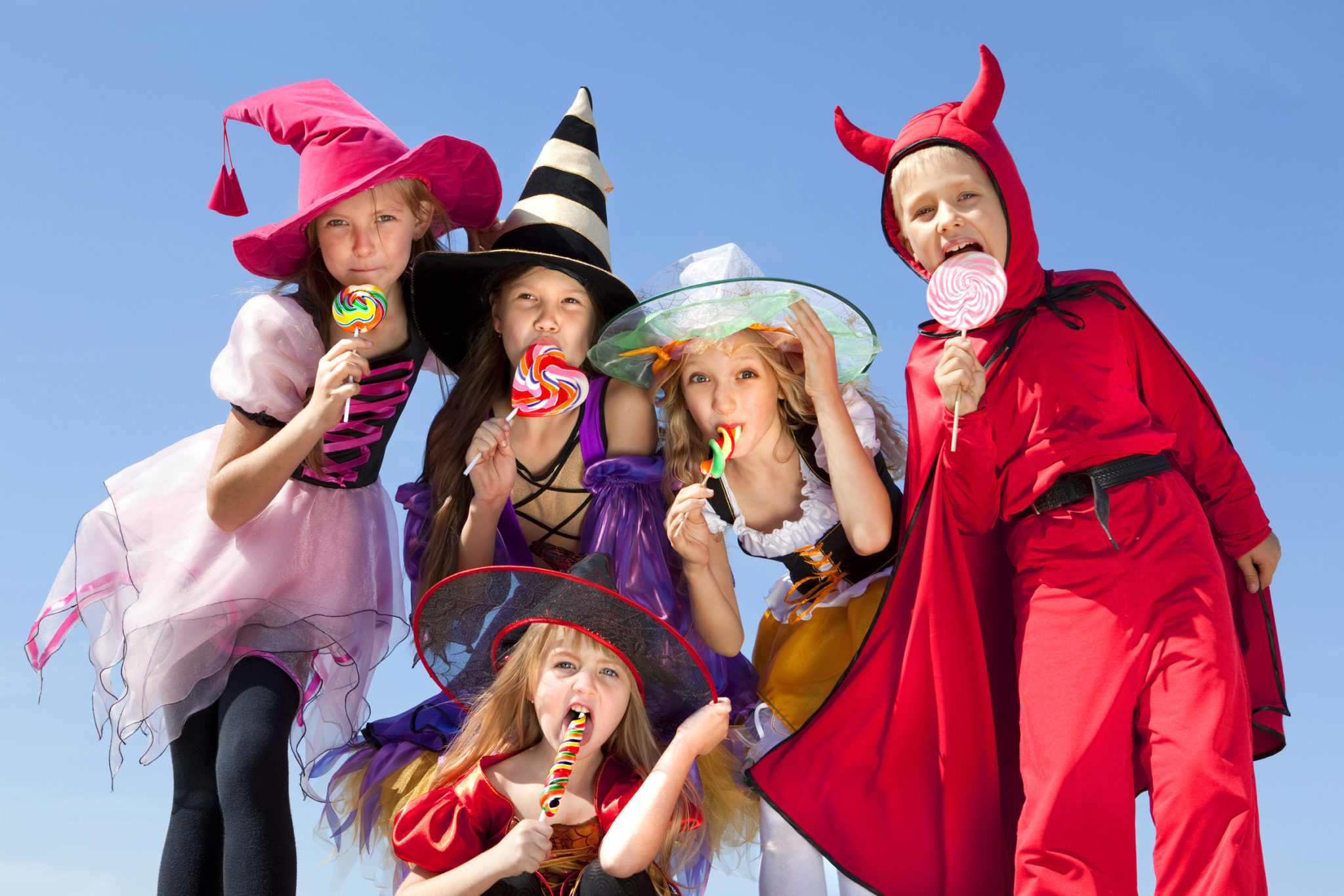 Five Children in Halloween Costumes Witches and Demon Licking their Candies.